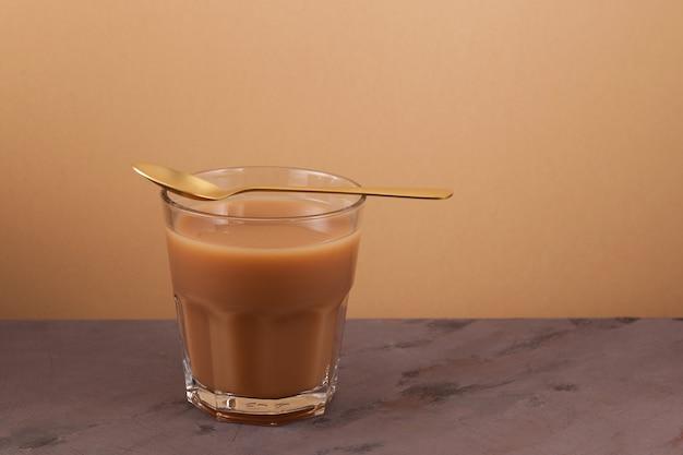 Chá masala chai ou karak em fundo marrom. bebida picante indiana tradicional.