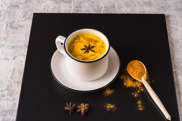 Chá masala chai tradicional indiano em uma caneca, anis e especiarias badian sobre a mesa branca.