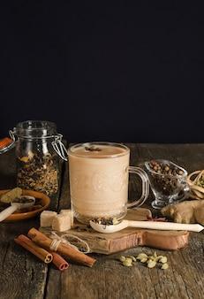 Chá masala com especiarias em fundo preto com espaço de cópia, bebida de aquecimento da índia