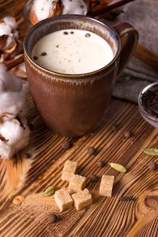 Chá masala em uma mesa de madeira ao lado de açúcar de cana.