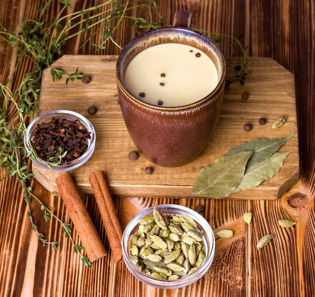 Chá masala em uma mesa de madeira ao lado dos ingredientes.