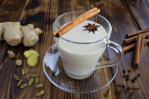 Chá masala no copo de vidro e ingredientes no fundo de madeira marrom. fechar-se.