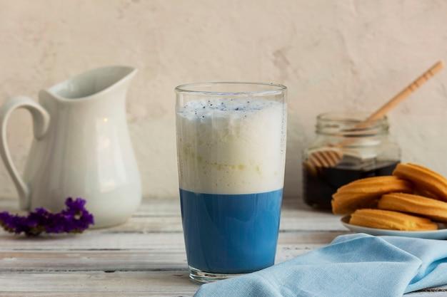 Chá matcha azul em um copo de café com leite em cima da mesa.