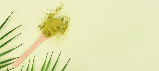 Chá matcha com colher e folha sobre fundo verde