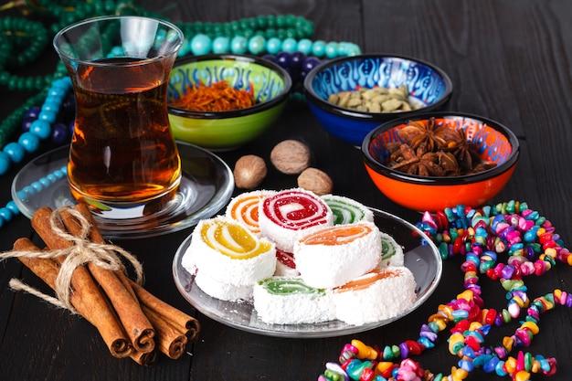 Chá no armudu tradicional do azerbaijão e pilha de doces na mesa