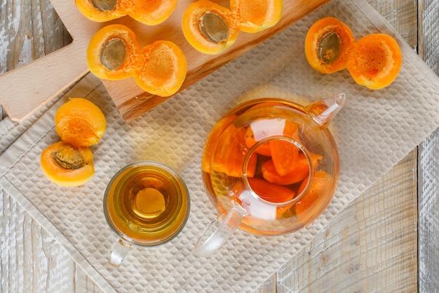 Chá no bule e caneca com damascos, vista superior de tábua na toalha de madeira e cozinha