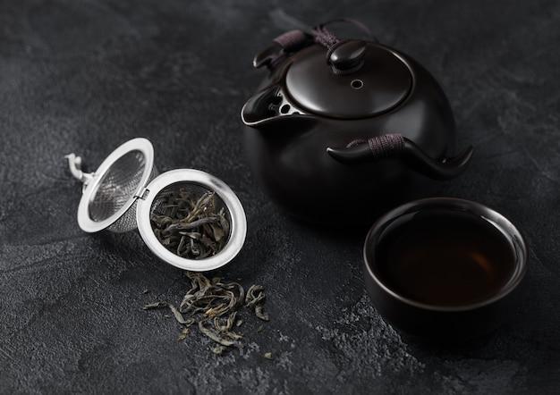 Chá orgânico verde solto em infusor de peneira e bule de cerâmica e xícara em fundo escuro.