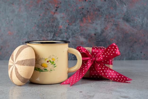 Chá perfumado de rosas para cachorro, um biscoito e um pacote de presente em superfície de mármore
