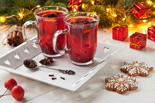 Chá picante quente na bandeja com galhos de árvores coníferas.
