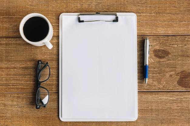 Chá preto; caneta; óculos e white papers em branco com prancheta em fundo de madeira