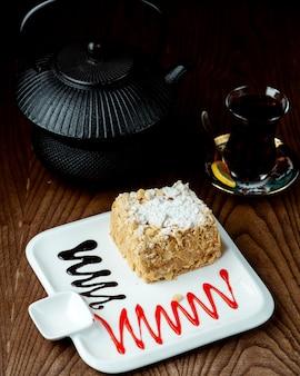 Chá preto com bolo napoleão em cima da mesa