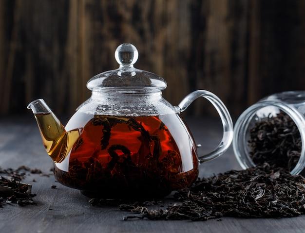 Chá preto com chá seco em um bule de chá na superfície de madeira, vista lateral