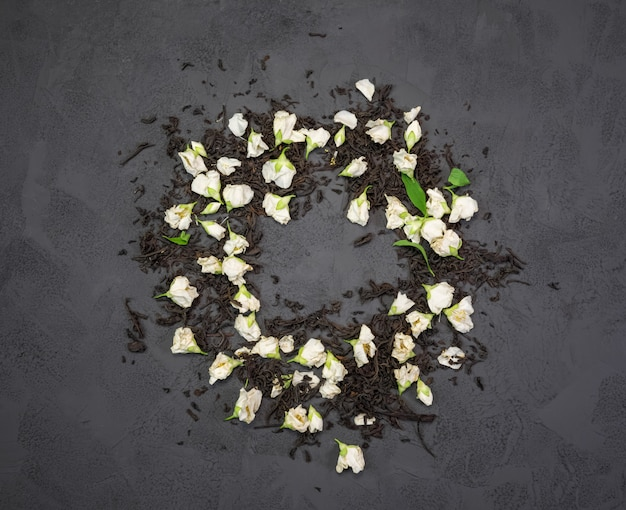 Chá preto com flores secas de jasmim em uma textura preta