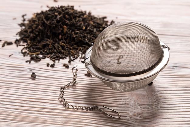 Chá preto com infusor de chá de bola de malha de aço no fundo de madeira
