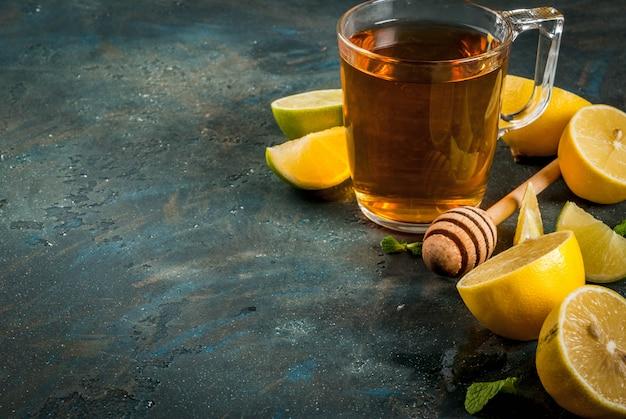 Chá preto com limão e hortelã na pedra de concreto azul escuro, copyspace