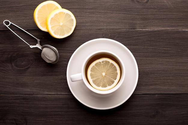 Chá preto com limão em uma mesa de madeira