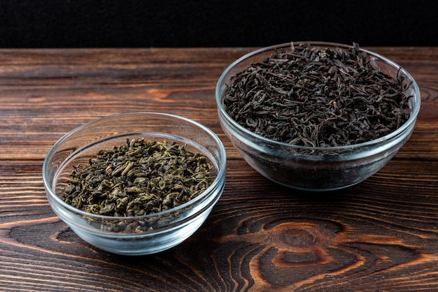 Chá preto e verde em fundo escuro de madeira.
