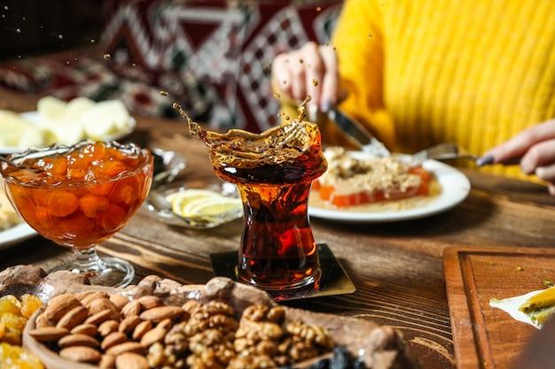 Chá preto em copo armudu com vários doces na mesa vista de perto