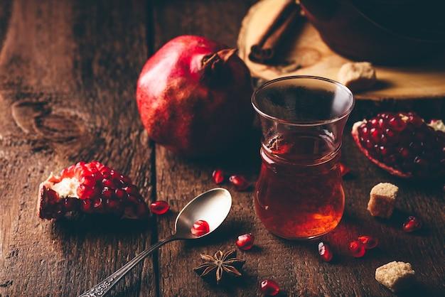 Chá preto em copo de chá árabe com romã fresca e alguns temperos na mesa de madeira