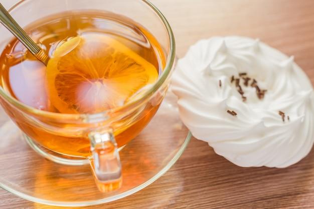 Chá preto em copo transparente um merengues caseiros de ar close-up