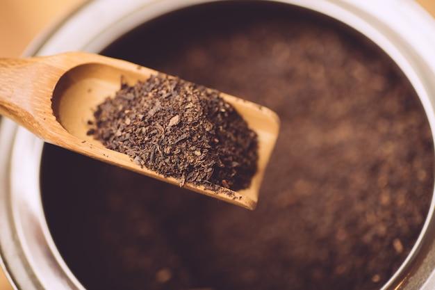 Chá preto em pó em uma colher de chá de madeira.