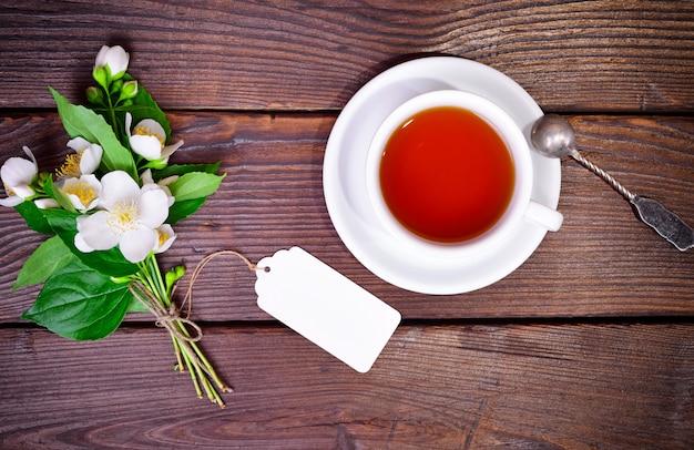 Chá preto em um copo redondo branco com um pires