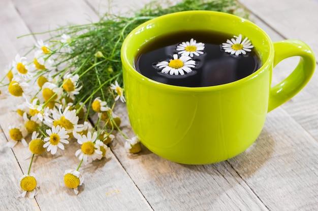 Chá preto em um copo verde sobre fundo de madeira e camomila
