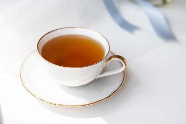 Chá preto em uma bela xícara de porcelana branca com um corte dourado. lindo sol. cerimônia do chá.