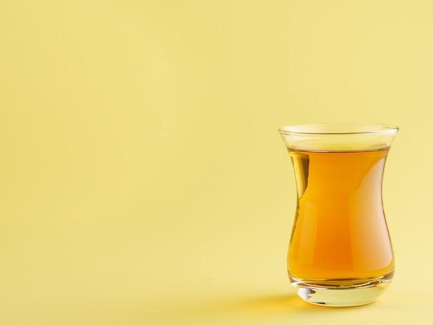 Chá preto em uma caneca tradicional turca em um fundo amarelo.