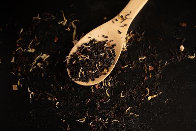 Chá preto em uma colher de pau em um fundo de chá preto. fechar-se.
