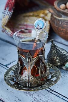 Chá preto em uma tradicional xícara de vidro e biscoitos na mesa de madeira azul
