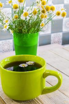 Chá preto em uma xícara verde sobre fundo de madeira e camomila