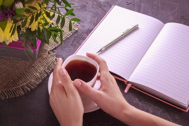 Chá preto nas mãos femininas em um copo branco com flores
