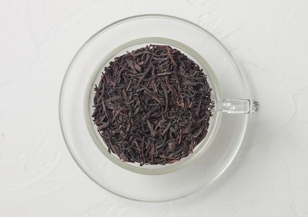 Chá preto orgânico em copo de vidro transparente sobre fundo branco. vista do topo