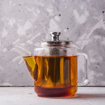 Chá preto ou masala em um bule em cinza