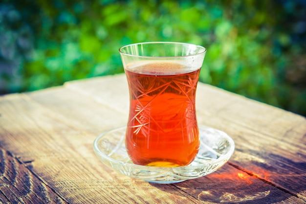 Chá preto perfumado em mesa de madeira no jardim