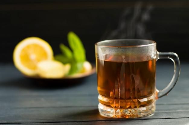 Chá preto quente com limão e hortelã, em copo de vidro, sobre fundo de madeira