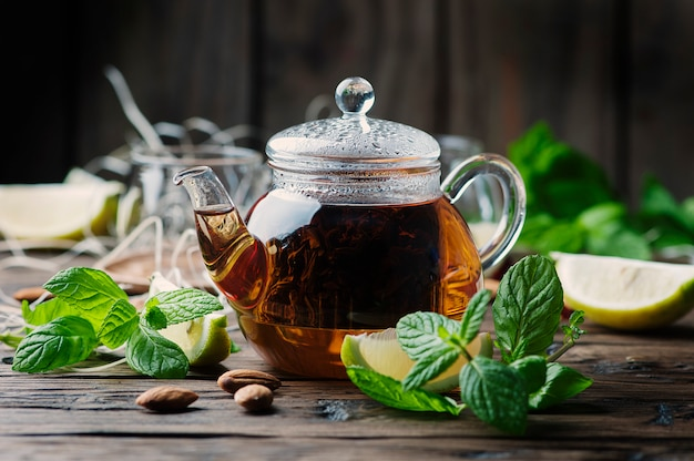 Chá preto quente com limão e hortelã na mesa de madeira