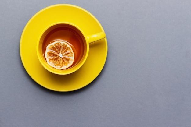 Chá preto quente com vista superior da fatia de limão na mesa cinza. copo amarelo em cinza. cores do ano 2021.