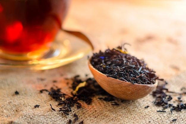 Chá preto seco em uma colher de pau e uma xícara de chá perfumado no fundo