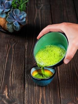 Chá profissional segurando uma tigela de chá tradicional asiático matcha feito na hora