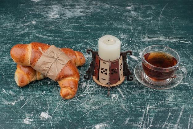 Chá quente com croissants e vela no mármore