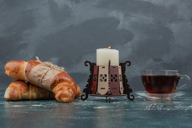 Chá quente com croissants e velas na mesa de mármore.