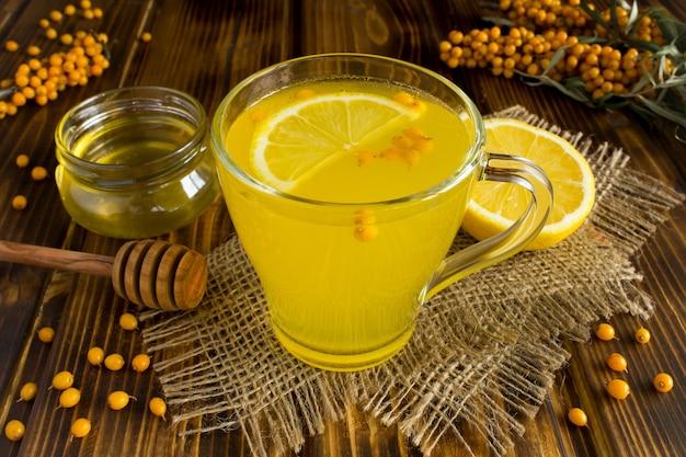 Chá quente com espinheiro, limão e mel no fundo de madeira rústico