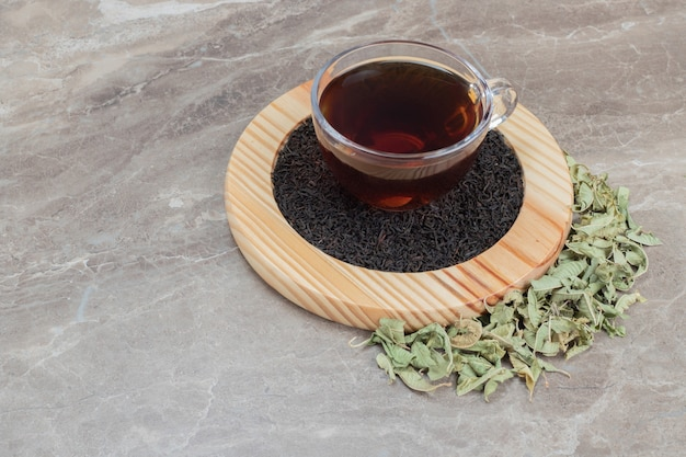 Chá quente com folhas secas na placa de madeira.