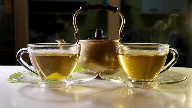 Chá quente com fumaça no copo de vidro sobre a mesa de madeira branca e bules de ouro.