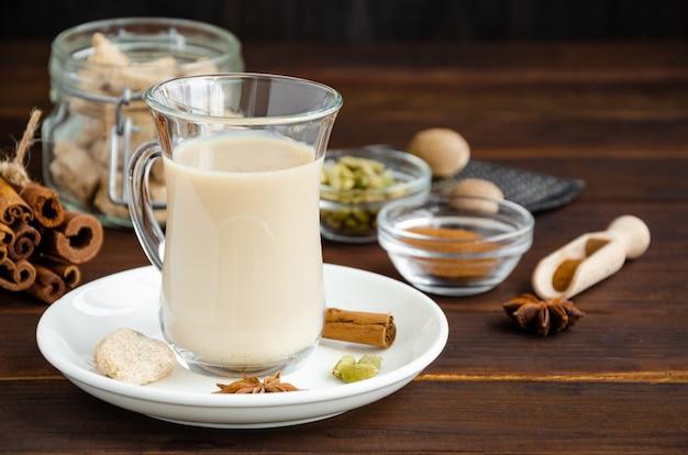 Chá quente com leite, canela, cardamomo, anis e outras especiarias, chá indiano masala em um copo de vidro com fundo de madeira. copie o espaço.