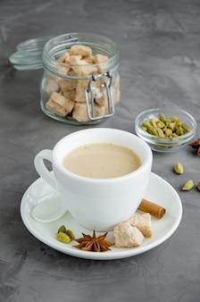 Chá quente com leite, canela, cardamomo, anis e outras especiarias, chá indiano masala em uma xícara branca sobre um fundo escuro. vertical, copie o espaço.
