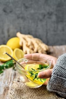 Chá quente com limão, gengibre e hortelã em uma caneca de vidro é segurado pela mão da menina