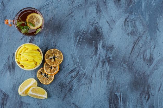 Chá quente com limões e tigela amarela de doces amarelos sobre fundo azul.